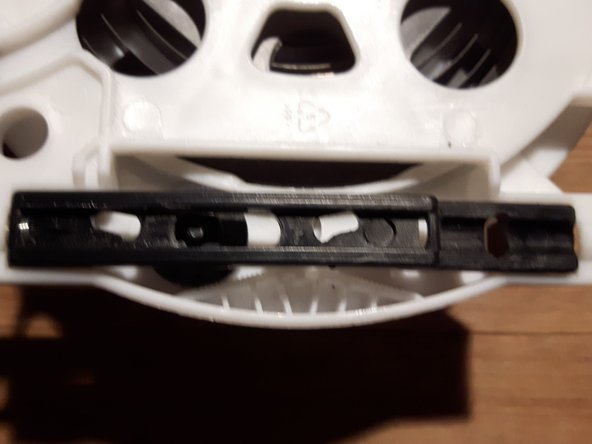 Da die Gummirolle nicht greift, diese herausnehmen, indem man den schwarzen Schieber mit der Feder über den weißen Zylinder hebelt (Plastik biegt, wird nicht kaputt gehen) und unter dem Steg rechts im Bild hervorhebeln.