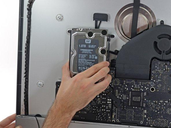 Fasse die Festplatte und linke Festplattenhalterung zusammen.