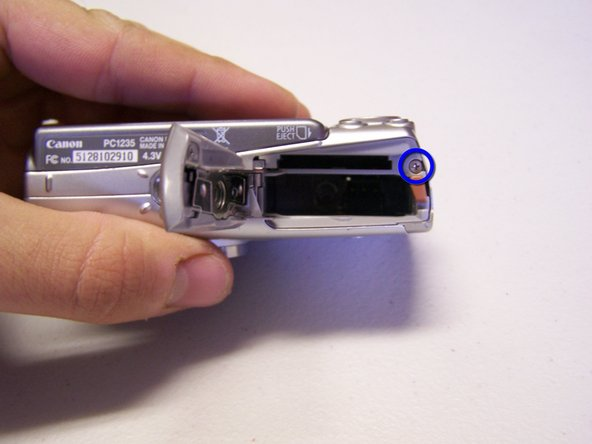 Image 2/3: Remove the screw in the battery port, indicated by the blue circle, again using a Phillips #00 screwdriver.