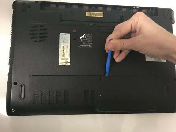 Remove the back cover by placing a plastic opening tool in the indention and prying upwards.