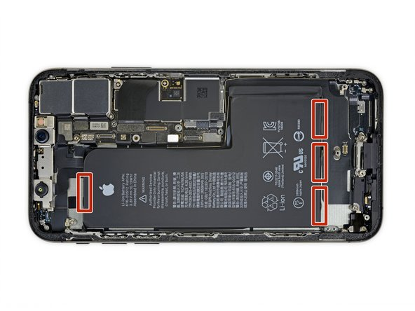 The battery is secured to the rear case by four pieces of stretch-release adhesive—one under the upper area of the battery, and three under the lower area.