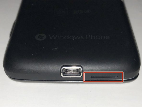 Remove the back cover of the device to access the internal components of the HTC 7 Surround.