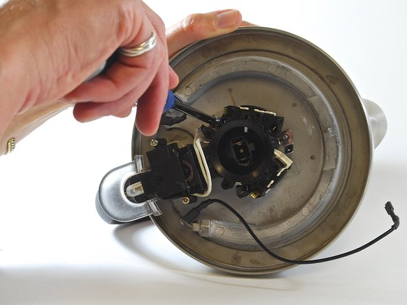 """Image 2/2: SECOND IMAGE: Roll the kettle over so the handle is now on your left. Use the 7/32"""" nut driver to remove the 7/32"""" nut from the final stud, which is now located counter-clockwise from where the power supply was attached."""