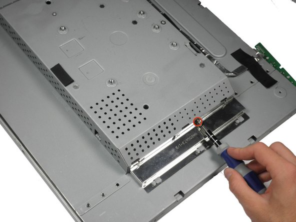 With the monitor facing down, remove the 5.84 mm Phillips #2 screw from the metal sheet.