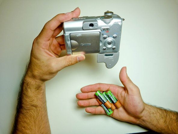 Turn the camera over and allow the batteries to fall out.