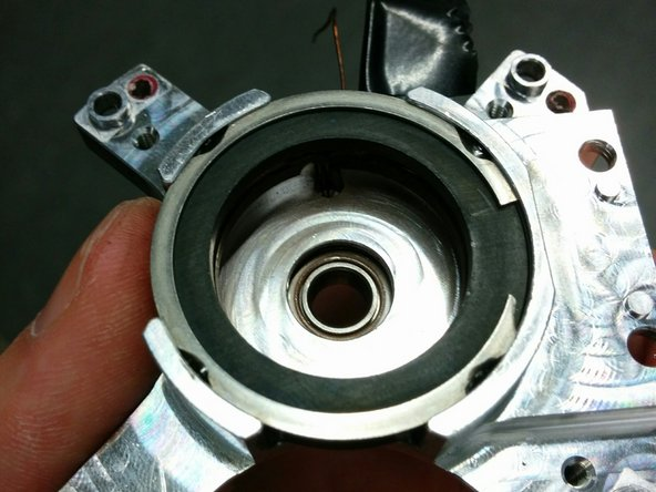 From the bottom of the bearing housing, push the bearing out. It shouldn't require that much force.
