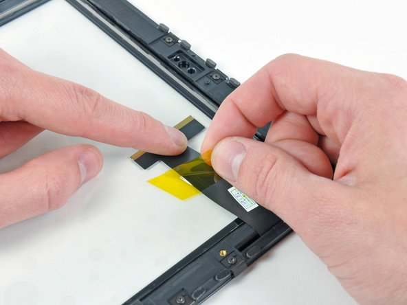 Remove the piece of yellow tape securing the digitizer cable to the inner face of the front panel assembly, being careful not to rip the cable in the process.
