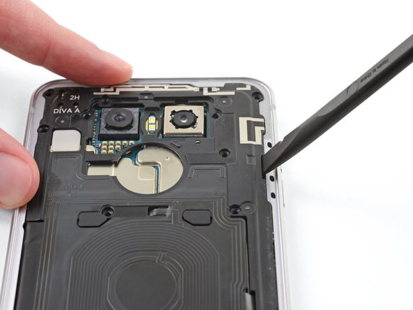 Insert the flat end of a spudger into the small gap between the upper antenna shield and the phone chassis and pry up, releasing the clips holding the shield in place.