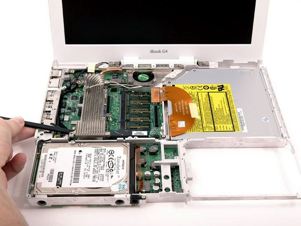 Image 1/1: Use a spudger to pry the heat sink up on the left side, near the hard drive.