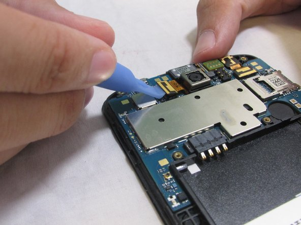 Carefully remove the camera's ribbon cable from the motherboard using the plastic removal tool.