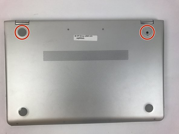 Use the plastic opening tool to remove the gray rubber pads on the bottom of the laptop. For our device we only needed to remove the two at the top.