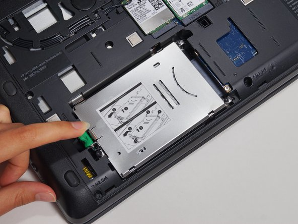 Pull the green tab away from the metal casing and lift the drive out.