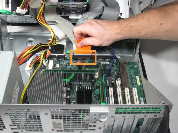 Disconnect the optical drive ribbon cable by gently pulling the orange tab away from the motherboard.