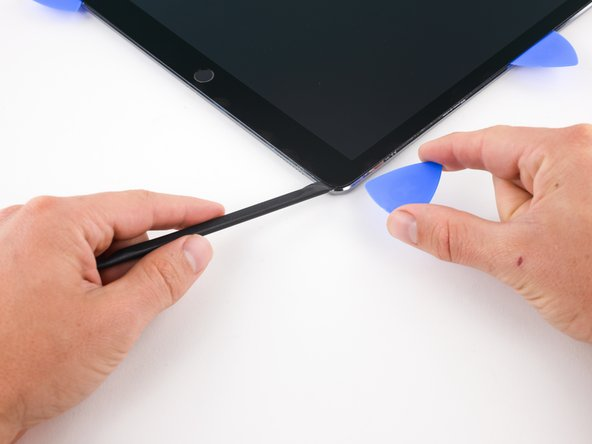 Image 1/2: Insert a pick in the lower right corner of the iPad where you slid the blade through.