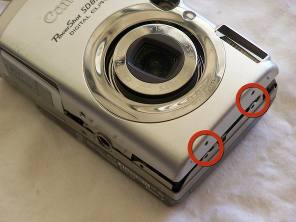 Image 1/3: Remove the two side screws, indicated by the red circles, using a Phillips #00 screwdriver.