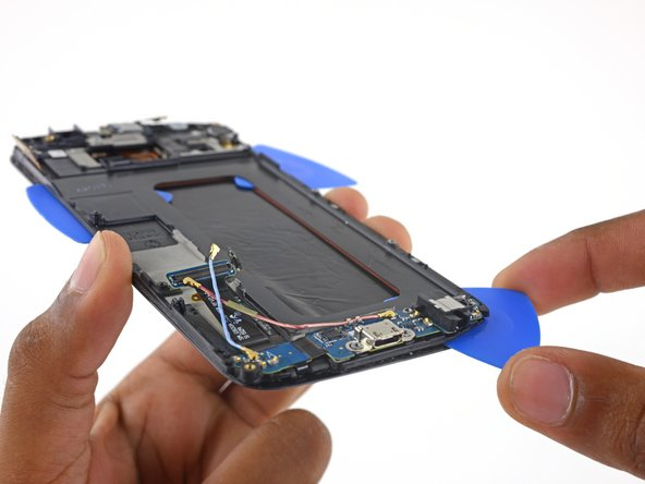Grasp the opening pick next to the headphone jack and slide it to the bottom right corner of the display frame.