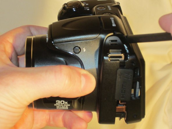 Using the spudger, move around the casing, carefully separating the rear housing from the camera assembly.