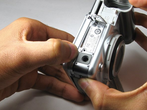 Slowly and gently pry open with your hands to separate the back case panel from the rest of the camera.