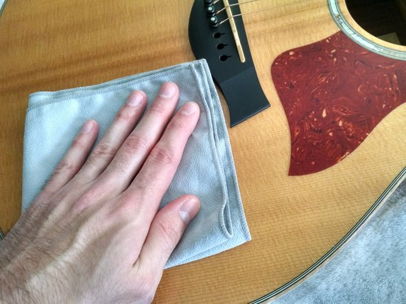 Spray two squeezes of Dunlop 65 Guitar Polish & Cleaner onto a clean microfiber cloth. It is important that you do not apply the spray directly to the guitar, as leaving large amounts of the solution on the guitar for too long can damage the finish.