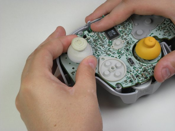 Grab the base of the grey joystick cover with one hand and firmly hold down the rest of the controller with the other hand.