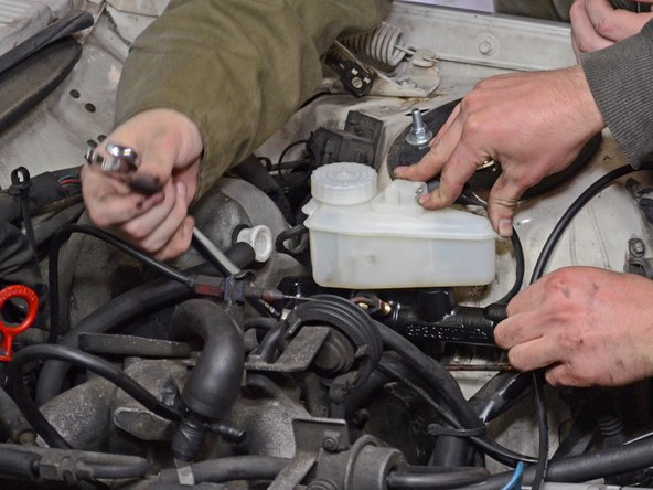 Image 2/2: Remove the brake master cylinder, taking care not to damage or bend the brake lines.
