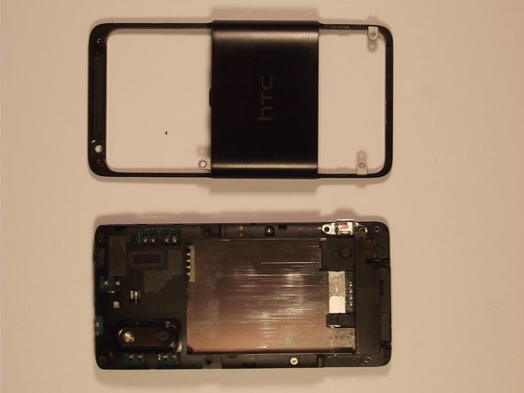 To remove the remaining cover, lift the side port, which was previously uncovered, then lift the outer shell from the bottom of the phone and slide it forward