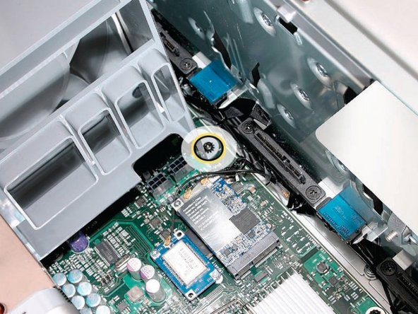Image 2/3: Remove the second Phillips screw at the bottom front of the assembly.