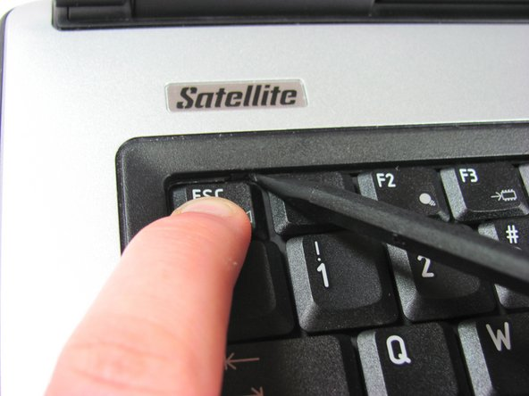 While you press down the ESC key, push the tab with the spudger to release that side of the keyboard.