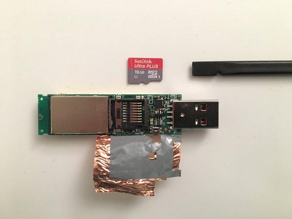 A l'aide d'un outil plastique pousser la carte SD vers le port USB (en vous aidant du décrochement sur le côté de la carte)