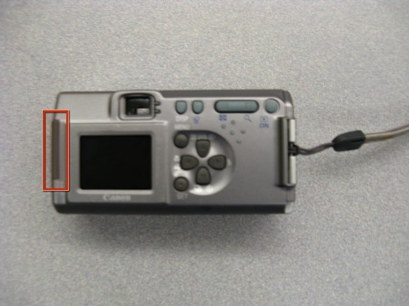 Hold the camera right side up with the LCD screen facing you.  Remove the screen battery located to the left of the screen. Set it aside.