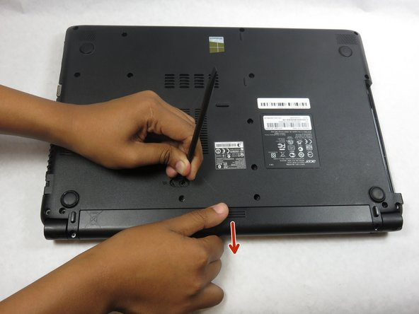 Take your other hand to slide the battery away from the laptop to remove.