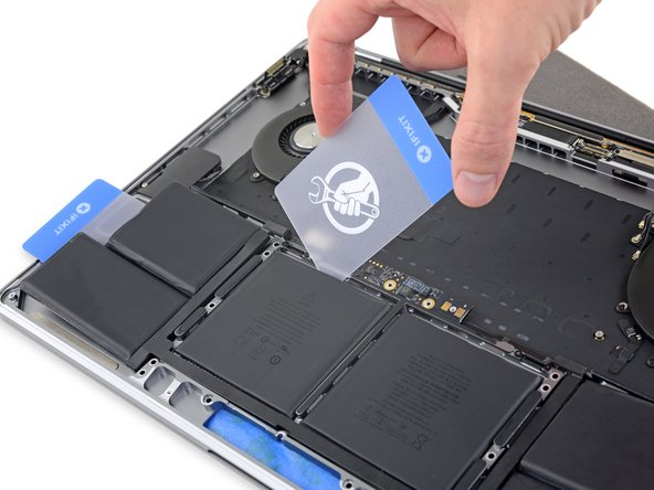 After a couple minutes, retrieve your first plastic card and insert one corner under the top edge of one of the center battery cells.