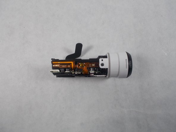 You'll see a screw on the top of the device, towards the front, remove this screw. Next pull the tabs on the bottom and top of the lens, and pull outward, this will remove the lens housing from the body. Once removed, flip the device onto its side, leaving the LCD display facing up.