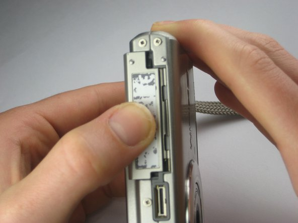 Grasping the camera tightly, press downward firmly on the piece with the label and slide it towards the LCD screen (to the left).