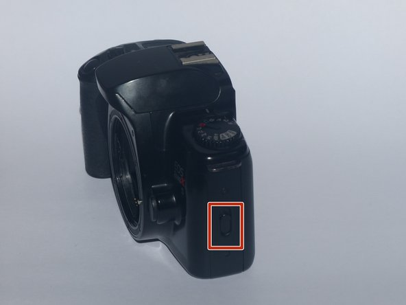 Push up on the switch on the right side of the camera (if you're facing the front of the camera) until you hear the clicking sound of the back latch opening.