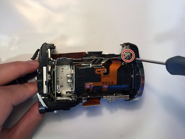 Remove the 3mm Phillips #00 screw from the underside of the camera near the lens housing.