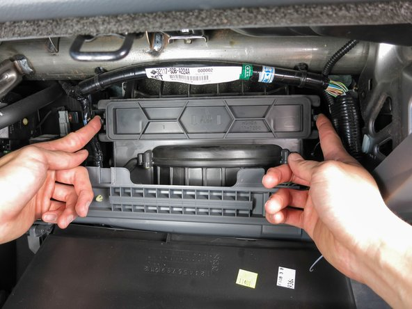 Press on both tabs of the cover and pull the cover outwards towards you to reveal the cabin air filter.