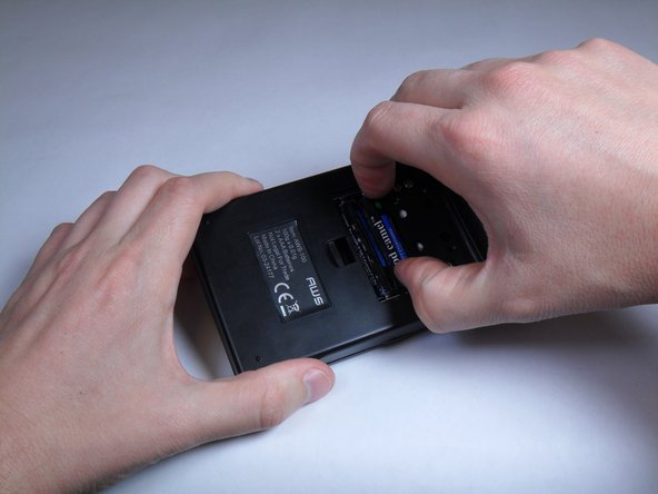 Use fingers to remove and replace both triple-A batteries.