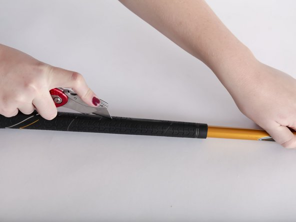 Image 2/2: Using a blade or knife, cut a line through the grip.