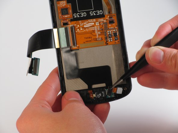Pull the black rectangular piece, attached to the front facing camera, away from the rear panel.