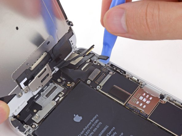 Use a plastic opening tool to disconnect the home button cable connector.