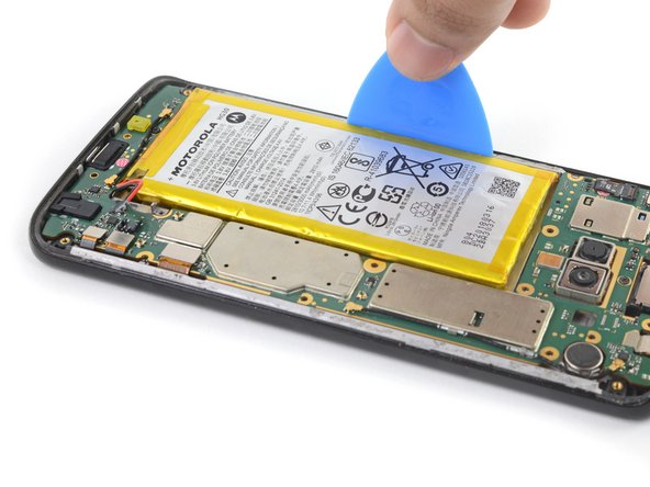 Use an opening pick to steadily pry the battery up, starting from the outer edge of the battery.