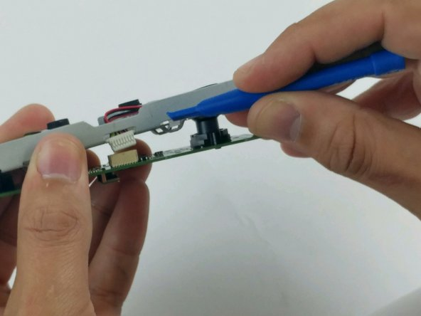 Using a plastic opening tool, disconnect the microphone array connector from the motherboard.