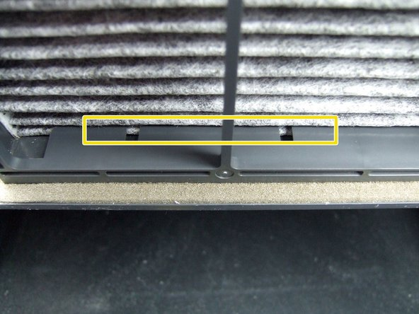 Image 2/2: Ensure that the  last vanes on the front and back of the filter fit into the retaining tabs in the filter tray.