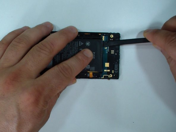 With a plastic tool carefully separate the battery from the logic board.