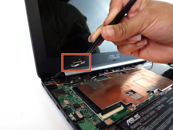 Locate the LCD cable and its connector which is located in the upper left hand corner of the computer.  Carefully flip up the tiny tab and  safely remove the cable using precision tweezers.