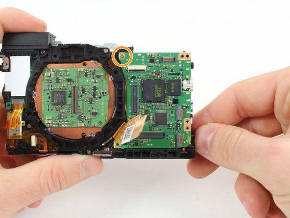 Image 2/3: Do not try to remove the motherboard from the camera yet.