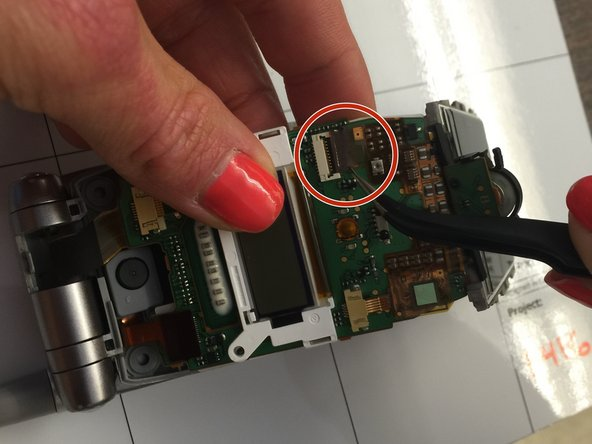 On the circuit board, release the two connector ribbons holding the screen to the circuit board.  To do this use tweezers to disconnect both the off-white connector piece and the white connector piece.
