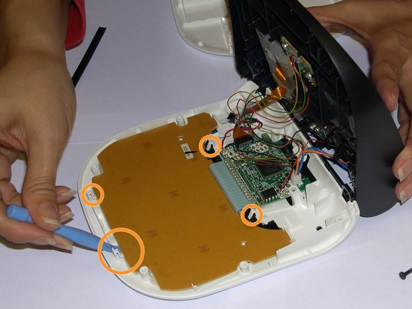 After removing the last three Philips screws, the keyboard has to be removed. To do so, you'll have to hold it making sure the four hooks with orange circles are properly loose to avoid breaking them.