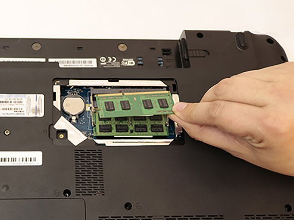 Push the two top tabs outwards and the top stick of RAM will pop up. Gently remove the stick of RAM by pulling it out.
